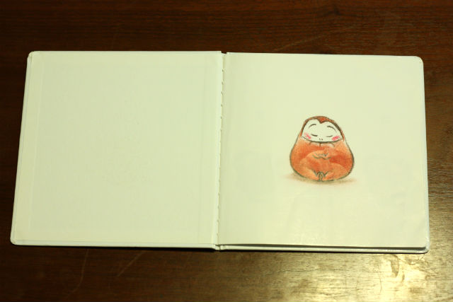 「だるまさんが」表紙を開いたページ。だるまさんがあぐらをかいて目を瞑っている